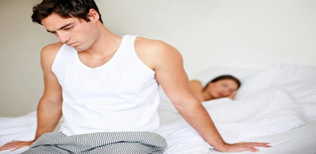man on bed battling with erectile dysfunction