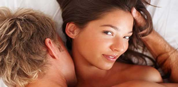 woman smiling in bed for oral sex