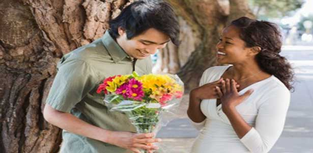 man shows her i love you with flowers