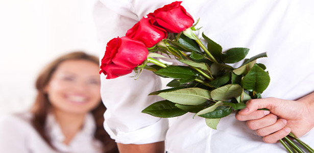 romantic man surprising woman with flowers