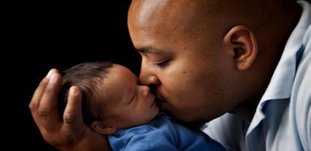 black dad kisses baby happy to see his kids